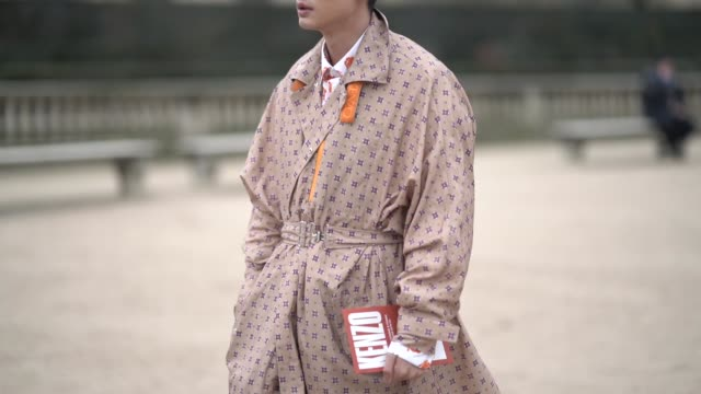 guest wears a geometrical pattern trench coat, a white shirt with orange floral print, black boots, beige pants, outside kenzo, during paris fashion... - トレンチコート点の映像素材/bロール