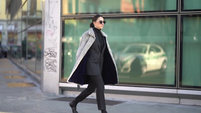A guest wears a gray coat sunglasses a blazer jacket a suit during Milan Menswear Fashion week Fall/Winter 2018/19 on January 13 2018 in Milan Italy