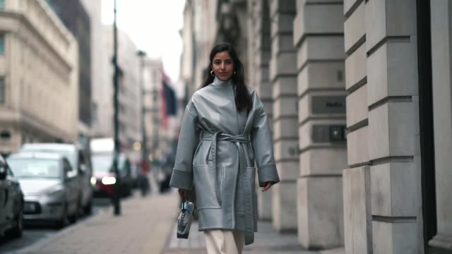 stockvideo's en b-roll-footage met a guest wears a gray winter coat a checked bag flare pants earrings during london fashion week february 2019 on february 16 2019 in london england - week