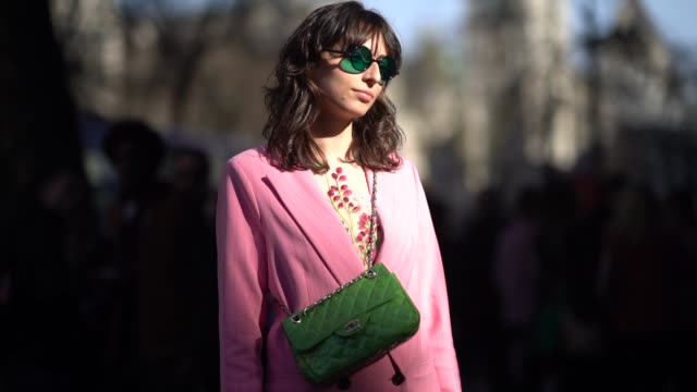 A guest wears a green chanel bag a pink suit sunglasses sneakers shoes during London Fashion Week February 2018 on February 16 2018 in London England