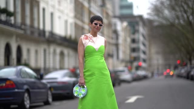 a guest wears a green dress and a bag during london fashion week february 2018 on february 18 2018 in london england - london fashion week stock videos and b-roll footage