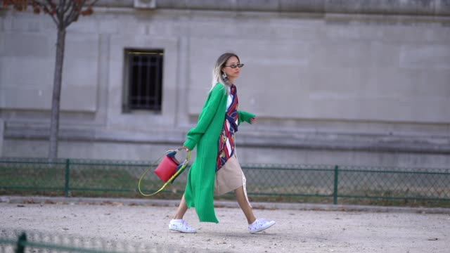 A guest wears a green jacket white sneakers a red bag outside Elie Saab during Paris Fashion Week Womenswear Spring/Summer 2019 on September 29 2018...