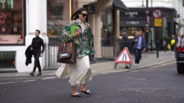 a guest wears a green jacket with printed flowers a vuitton bag with the inscription 'emily' a white ruffled skirt during london fashion week... - 彫刻画点の映像素材/bロール