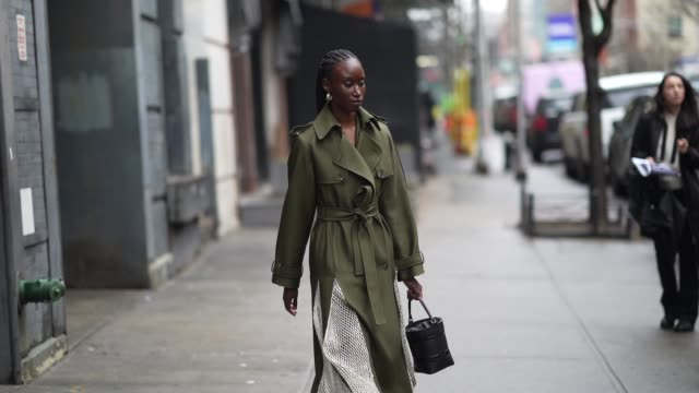 guest wears a green khaki long coat, earrings, black leather pointy boots, during new york fashion week fall winter 2020, on february 11, 2020 in new... - street style stock videos & royalty-free footage