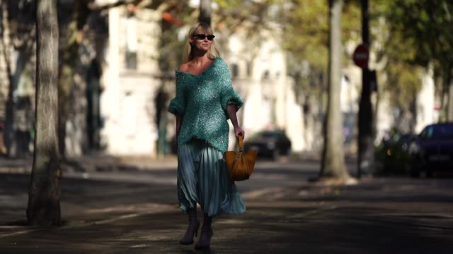 stockvideo's en b-roll-footage met a guest wears a green oversized glitter green top an orange bag a pleated skirt gray heels shoes during paris fashion week womenswear spring/summer... - hoge hakken