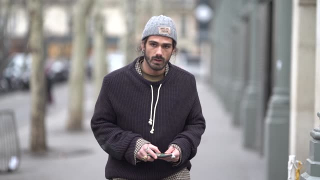 stockvideo's en b-roll-footage met guest wears a grey beanie hat, a black sweater with a sliding collar, a brown checkered suit with cuffed pants, brown platform shoes, outside acne... - manchet mouw