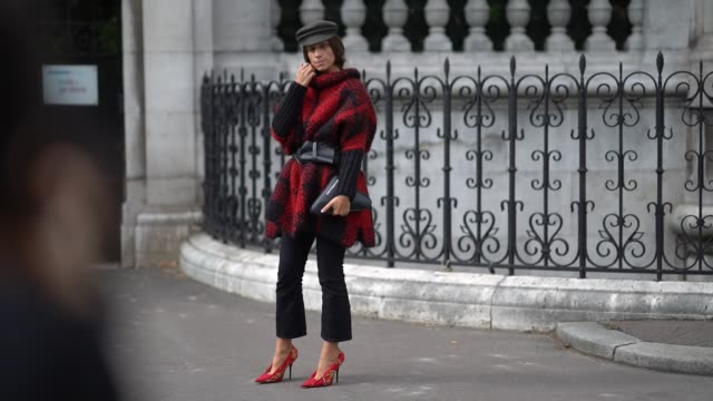 stockvideo's en b-roll-footage met a guest wears a grey hat a wooly turtleneck red and black coat a large black belta black bag black pants yellow and red stilettos outside the dries... - coltrui