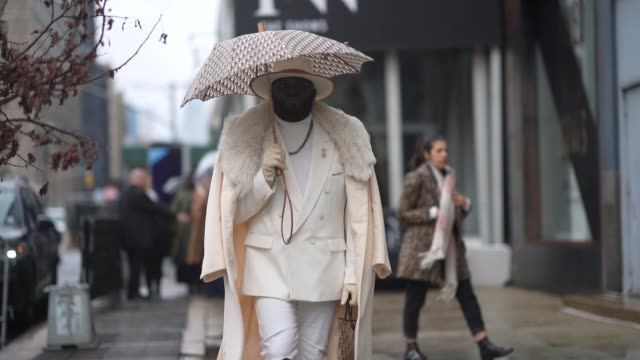 guest wears a hat, a dior monogram umbrella, a white double breasted jacket, a long coat with a faux fur fluffy part, a dior monogram bag, white... - hat stock videos & royalty-free footage