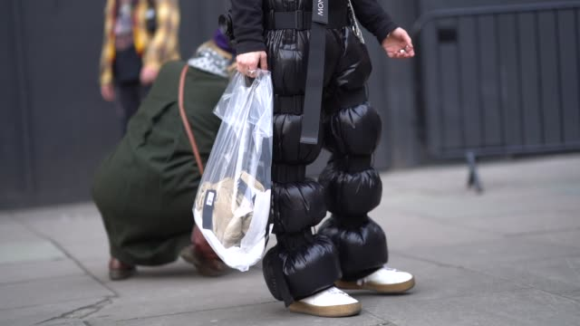 A guest wears a hat black puffer plastic pants during London Fashion Week Men's January 2018 at on January 06 2018 in London England