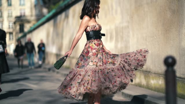 A guest wears a lace pleated dress with colored embroidered flowers a black large leather belt a green bag Lady Dior outside Dior during Paris...