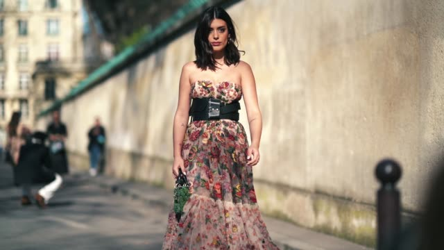 vídeos y material grabado en eventos de stock de a guest wears a lace pleated dress with colored embroidered flowers a black large leather belt a green bag lady dior outside dior during paris... - vestido