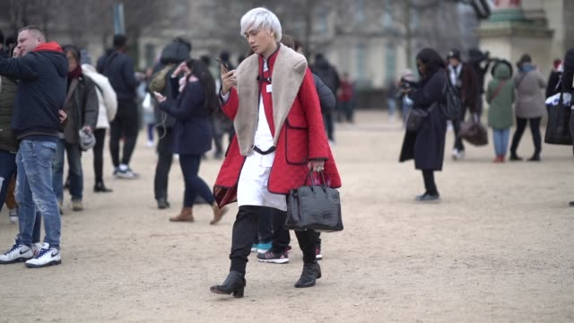a guest wears a large fur collar a red padded coat with black hem a white shirt black pants black boots with separate end a large black handbag... - white shirt stock videos & royalty-free footage