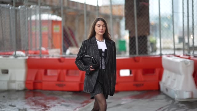 guest wears a leather bag, an oversized black striped jacket, shorts, tights, pointy shoes, during new york fashion week fall winter 2020, on... - shorts stock videos & royalty-free footage