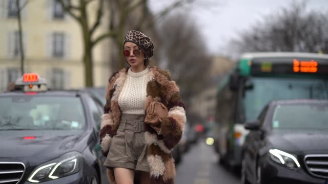 A guest wears a leopard print beret hat a brown fur coat a white wool pull over a skirt white boots during Paris Fashion Week Womenswear Fall/Winter...
