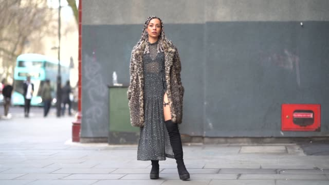 A guest wears a leopard print coat a leopard print lace dress black bras black boots during London Fashion Week Men's January 2018 at on January 06...