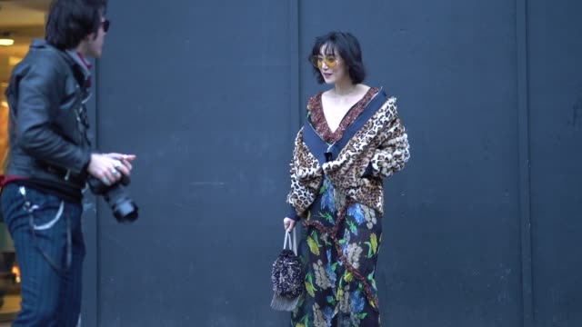 A guest wears a leopard print jacket a flower print dress yellow clear sunglasses black leather boots during London Fashion Week Men's January 2018...