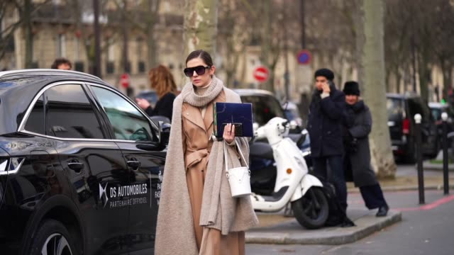 guest wears a long gray wool scarf, sunglasses, a brown leather trench coat, a white bag, outside leonard, during paris fashion week - womenswear... - トレンチコート点の映像素材/bロール