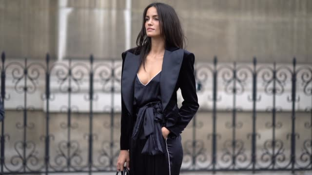 a guest wears a low neck silky top a balck jacket black pants mesh shoes outside redemption during paris fashion week womenswear spring summer 2020... - 低い点の映像素材/bロール