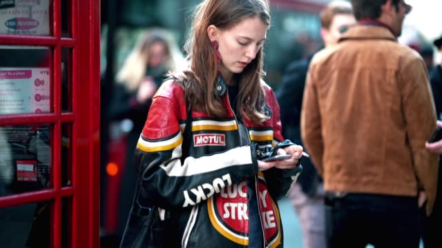 A guest wears a Lucky Strike red and black biker leather jacket black shoes cropped jeans and is smoking during London Fashion Week Men's January...