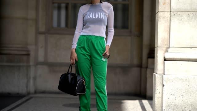 A guest wears a mesh top Calvin black bra Adidas green sportswear pants a Prada bag and black boots outside the Louis Vuitton show during Paris...