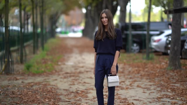 A guest wears a navy blue top midnight blue pants highheeled midnight blue slippers a white bag outside the Rochas show during Paris Fashion Week...