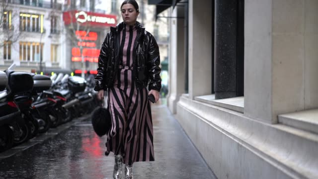 A guest wears a pink and black striped dress during Paris Fashion Week Haute Couture Spring Summer 2020 on January 23 2019 in Paris France