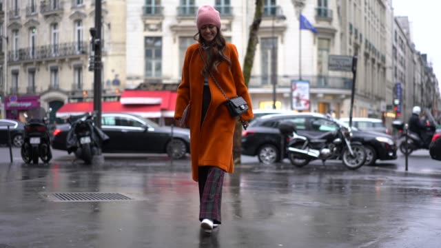 A guest wears a pink beanie hat an orange coat a Chanel bag checked flared pants white shoes during Paris Fashion Week Haute Couture Spring Summer...