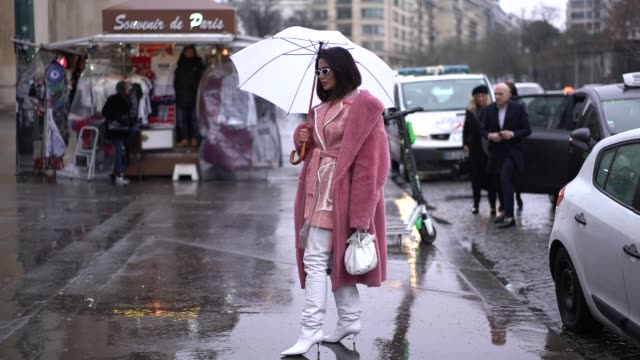 guest wears a pink fluffy coat, a pink jacket, white high boots, a white bag, holds an umbrella, outside elie saab, during paris fashion week - haute... - fluffy stock videos & royalty-free footage