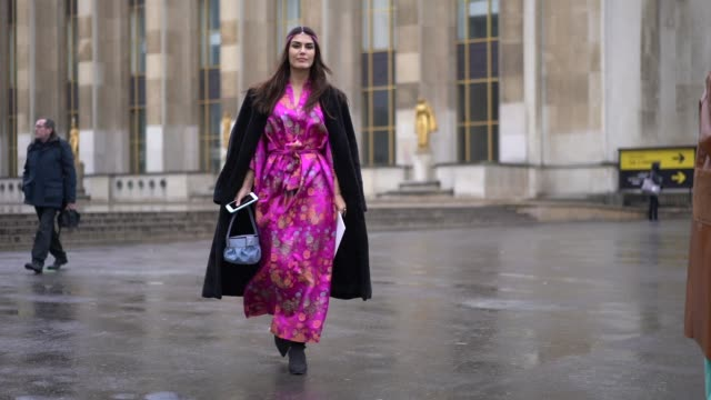 A guest wears a pink headband a pink satin floral print kimono dress blue jeans a blue bag during Paris Fashion Week Haute Couture Spring Summer 2020...