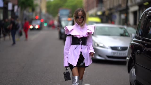 guest wears a pink ruffled top, a black large belt, silver thigh high boots, a black skirt, a black bag, outside topshop, during london fashion week... - thigh stock videos & royalty-free footage