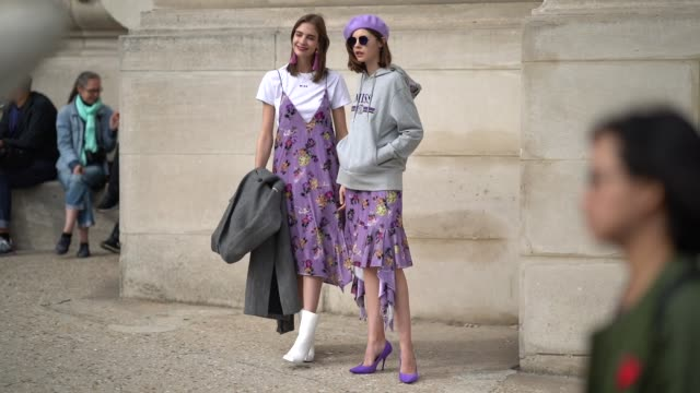 A guest wears a purple beret hat a gray hoodie a purple pleated skirt purple shoes sunglasses outside Margiela during Paris Fashion Week Womenswear...