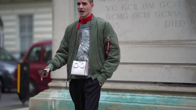 a guest wears a red bandanna a green bomber jacket a white bag during london fashion week february 2018 on february 18 2018 in london england - london fashion week stock videos and b-roll footage