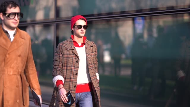 A guest wears a red beanie hat a checked coat white sneakers ripped jeans during Milan Menswear Fashion week Fall/Winter 2018/19 on January 13 2018...
