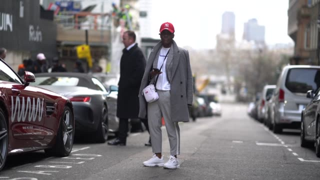 guest wears a red cap, a gray coat, a white bag, a white t-shirt, sportswear pants, white sneakers, during london fashion week men's january 2018 at... - all shirts点の映像素材/bロール