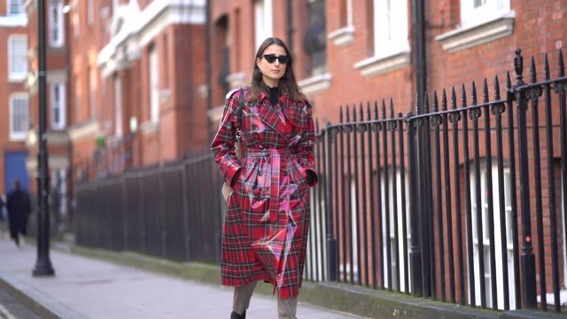 a guest wears a red checked pvc coat sunglasses during london fashion week february 2018 on february 17 2018 in london england - london fashion week stock videos and b-roll footage