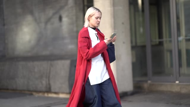 guest wears a red coat, a blue bag, a white top, blue flared denim pants, sneakers shoes, during london fashion week february 2019 on february 15,... - ストリートスナップ点の映像素材/bロール