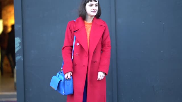 A guest wears a red coat a blue bag blue pants green shoes during London Fashion Week Men's January 2018 on January 07 2018 in London England