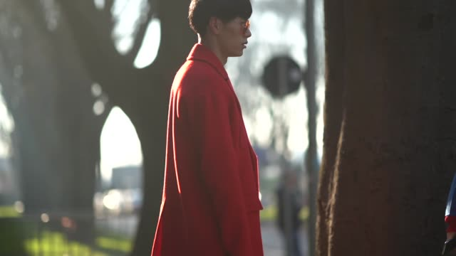 A guest wears a red coat a Prada clutch during Milan Menswear Fashion week Fall/Winter 2018/19 on January 13 2018 in Milan Italy