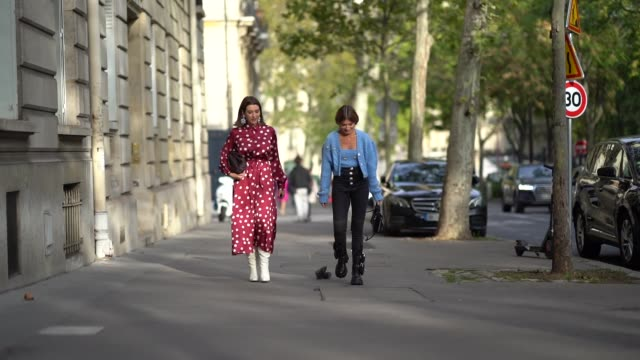 stockvideo's en b-roll-footage met a guest wears a red dress with printed polka dots and white boots a guest wears a blue vest a blue top black pants outside alessandra rich during... - stippen