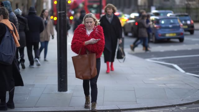 A guest wears a red faux fur coat a brown bag a turtleneck during London Fashion Week Men's January 2018 on January 07 2018 in London England
