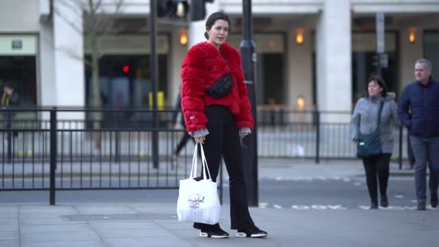 guest wears a red faux fur coat, during london fashion week men's january 2018 on january 07, 2018 in london, england. - london fashion week点の映像素材/bロール