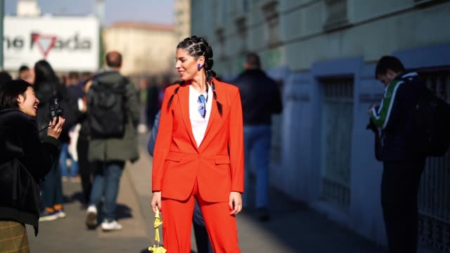 vídeos de stock, filmes e b-roll de guest wears a red jacket, a white t-shirt, blue glasses, a yellow bag, red pants, outside msgm, during milan fashion week fall/winter 2020-2021 on... - camiseta