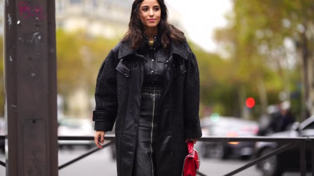 stockvideo's en b-roll-footage met a guest wears a red miu miu bag a black oversized leather coat red shoes outside miu miu during paris fashion week womenswear spring/summer 2019 on... - week