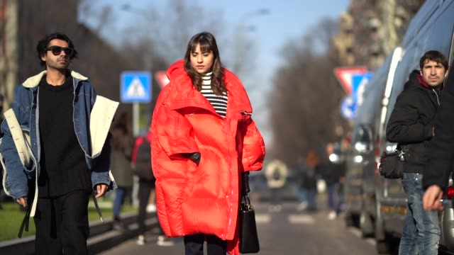 A guest wears a red oversized puffer coat a Dior bag during Milan Menswear Fashion week Fall/Winter 2018/19 on January 13 2018 in Milan Italy