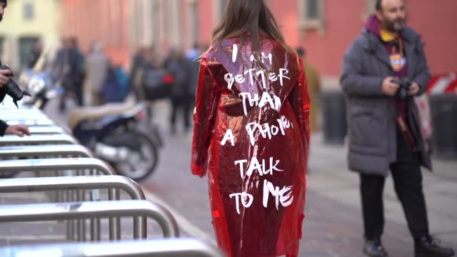 A guest wears a red plastic coat with a printed sentence 'I am better than a phone talk to me' during Milan Menswear Fashion week Fall/Winter 2018/19...