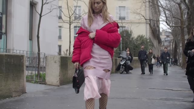 a guest wears a red puffer jacket a pink skirt fishnet tights black leather boots and a black bag outside the valentin yudashkin show during paris... - fishnet stock videos and b-roll footage