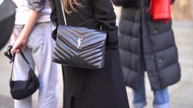 A guest wears a Saint Laurent YSL bag during Milan Menswear Fashion week Fall/Winter 2018/19 on January 14 2018 in Milan Italy