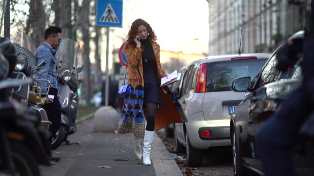 guest wears a saint laurent ysl blue shiny bag, a flower print coat, a pleated skirt, a turtleneck, white boots, during milan menswear fashion week... - dolcevita video stock e b–roll