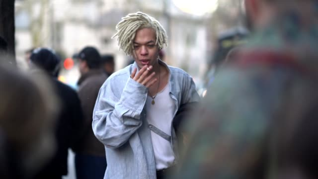 guest wears a shirt and is smoking, during london fashion week men's january 2018 on january 07, 2018 in london, england. - london fashion week点の映像素材/bロール
