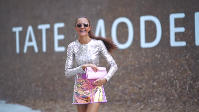 stockvideo's en b-roll-footage met a guest wears a silver glitter top a shiny skirt a pink clutch heels shoes during london fashion week september 2018 on september 17 2018 in london... - hoge hakken